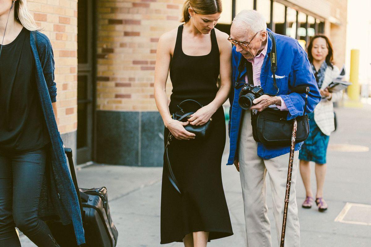 Fashion photographer Bill Cunnigham talking to a woman in a black dress on the sidewalk.
