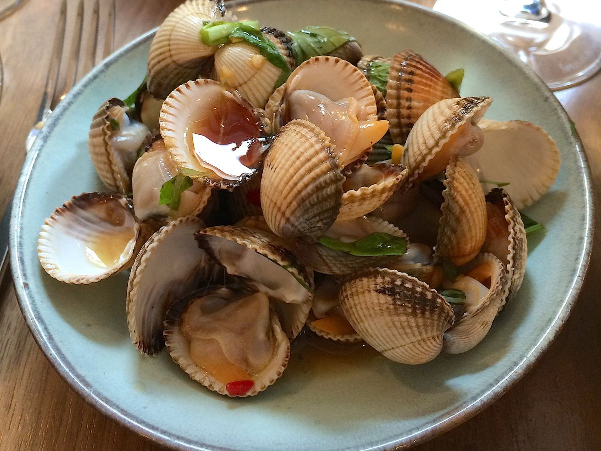 A bowl of clams topped with sauce and garnish