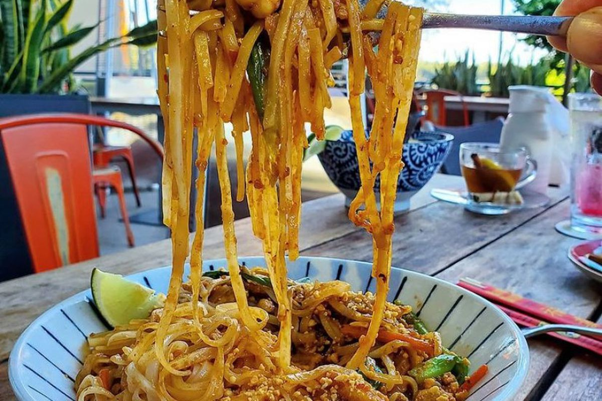 a hand holding a fork wrapped in long noodles which look like pad thai