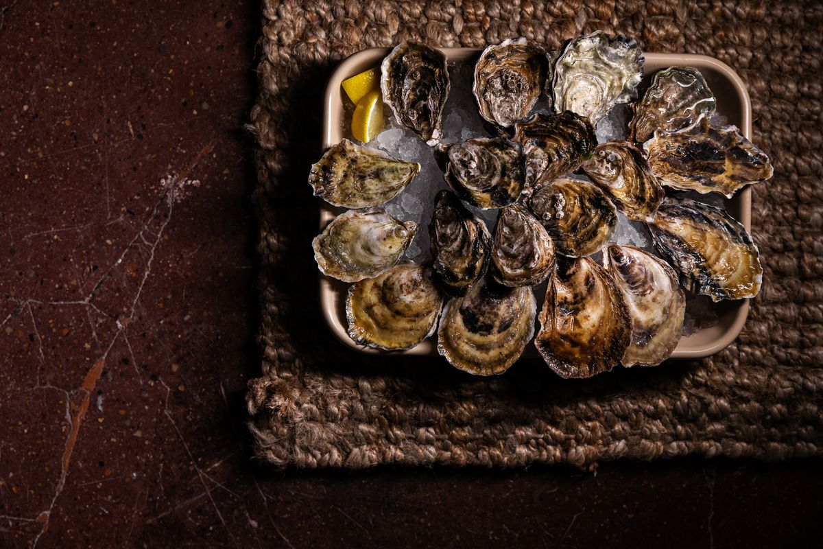 Oysters on a curved rectangular platter filled with ice sitting on a woven mat.