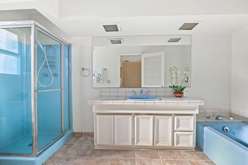 A bathroom with a blue shower enclosure and seaparate blue bathtub.