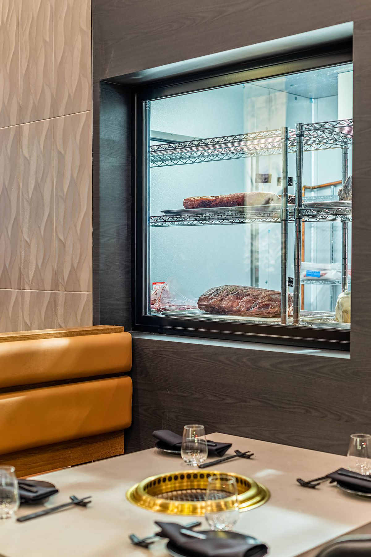 Dinner table setup at ABSteak with window into dry-aging room with beef.
