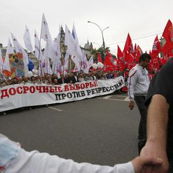 """Opposition supporters carry a poster reading """"For early election! Against repressions!"""" as they march heading for a protest rally in Moscow, Saturday, Sept. 15, 2012. Thousands of protesters marched across downtown Moscow on Saturday in the first major rally in three months against President Vladimir Putin, while defying the Kremlin's ongoing efforts to crackdown on opposition."""