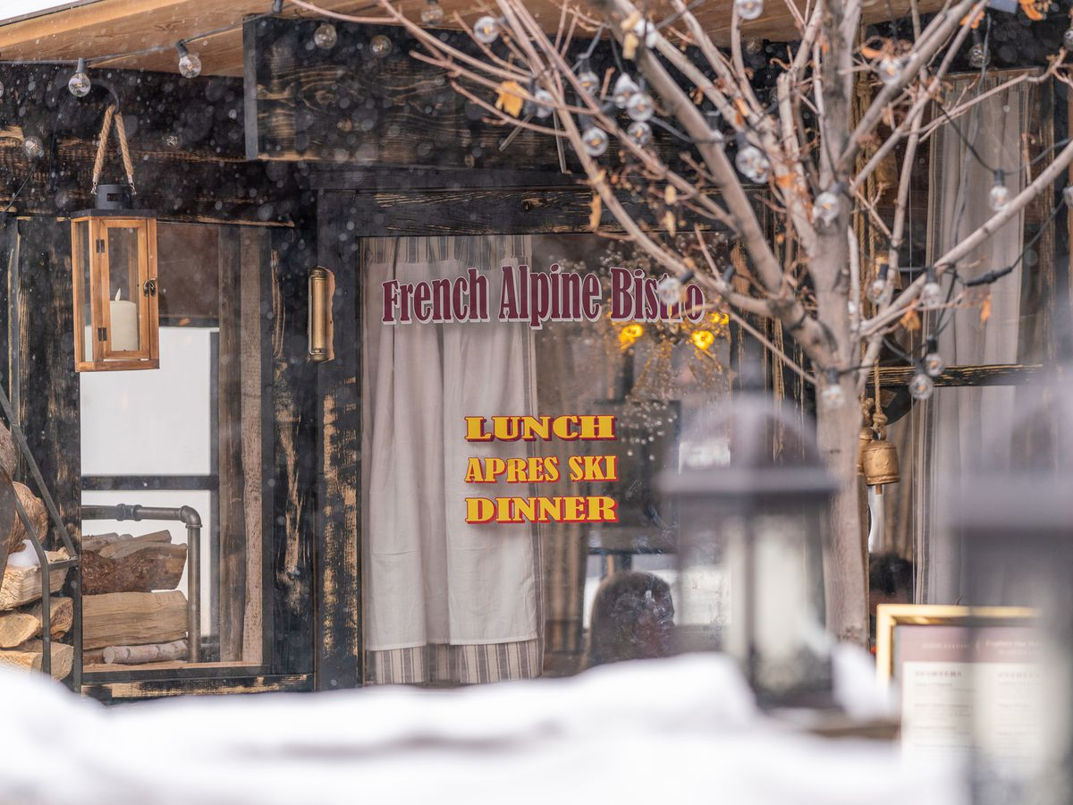 A restaurant window, in a snowy street scene, with the restaurant's name in bright lettering