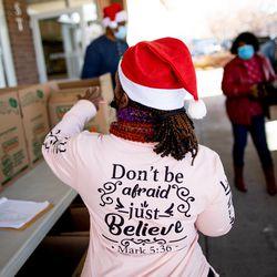 Yvonne Ryans helps direct volunteers as people come to pick up foodat Calvary Baptist Church in Salt Lake City on Saturday, Dec. 19, 2020.