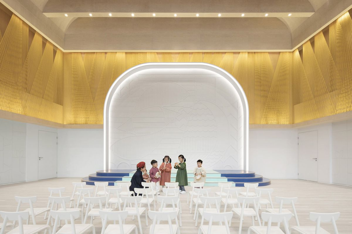 Children in room with stage, white chairs, and golden wall treatment in the back.