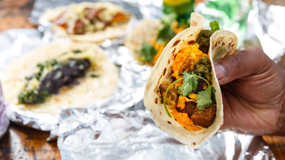 A hand holds a breakfast taco with meat, cheese, and chorizo while other breakfast tacos on foil wrappers are set on a table in the background