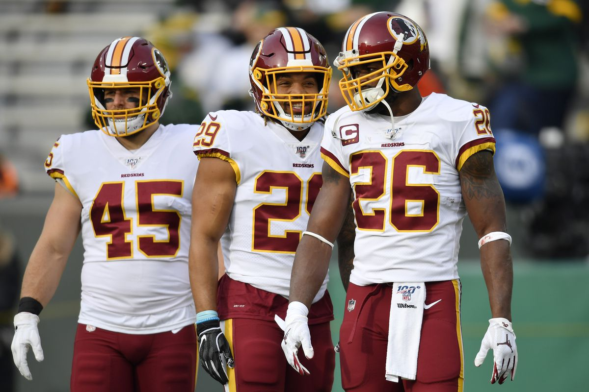 Derrius Guice #29 and Adrian Peterson #26 of the Washington Redskins discuss before the game against the Green Bay Packers at Lambeau Field on December 08, 2019 in Green Bay, Wisconsin.
