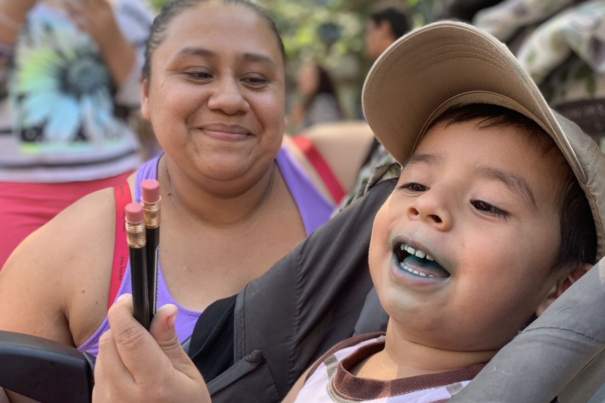 Maria Garcia and her son Leonardo wait in line for free school supplies at the first back to school bash.
