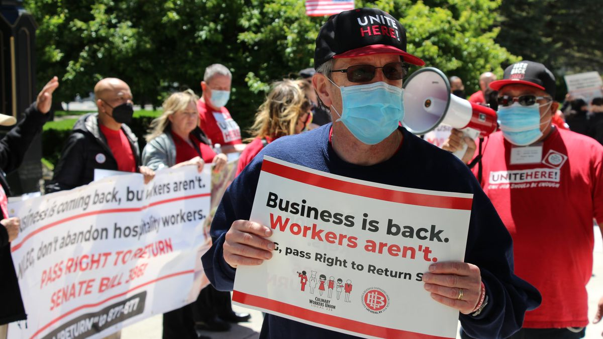 People wearing masks carry signs