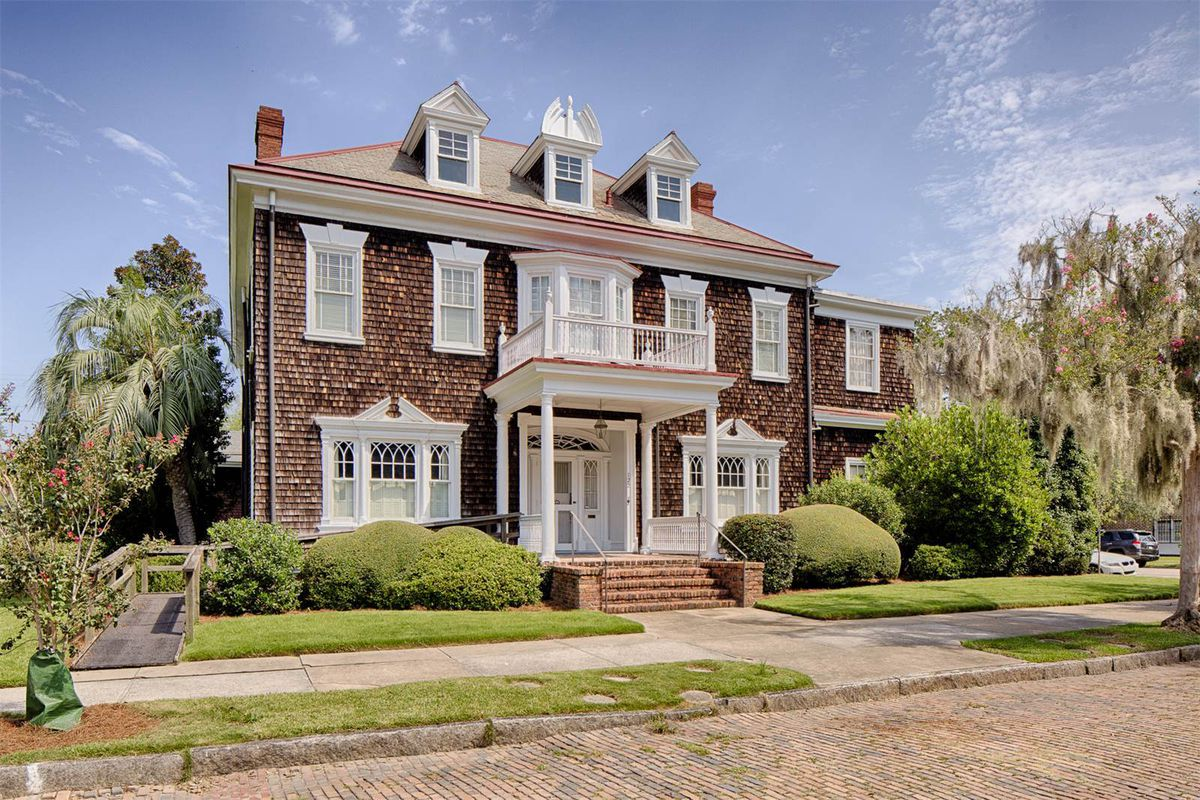 Colonial Revival home with shingled exterior and white window treatments and porticoed entrance sits on the street.