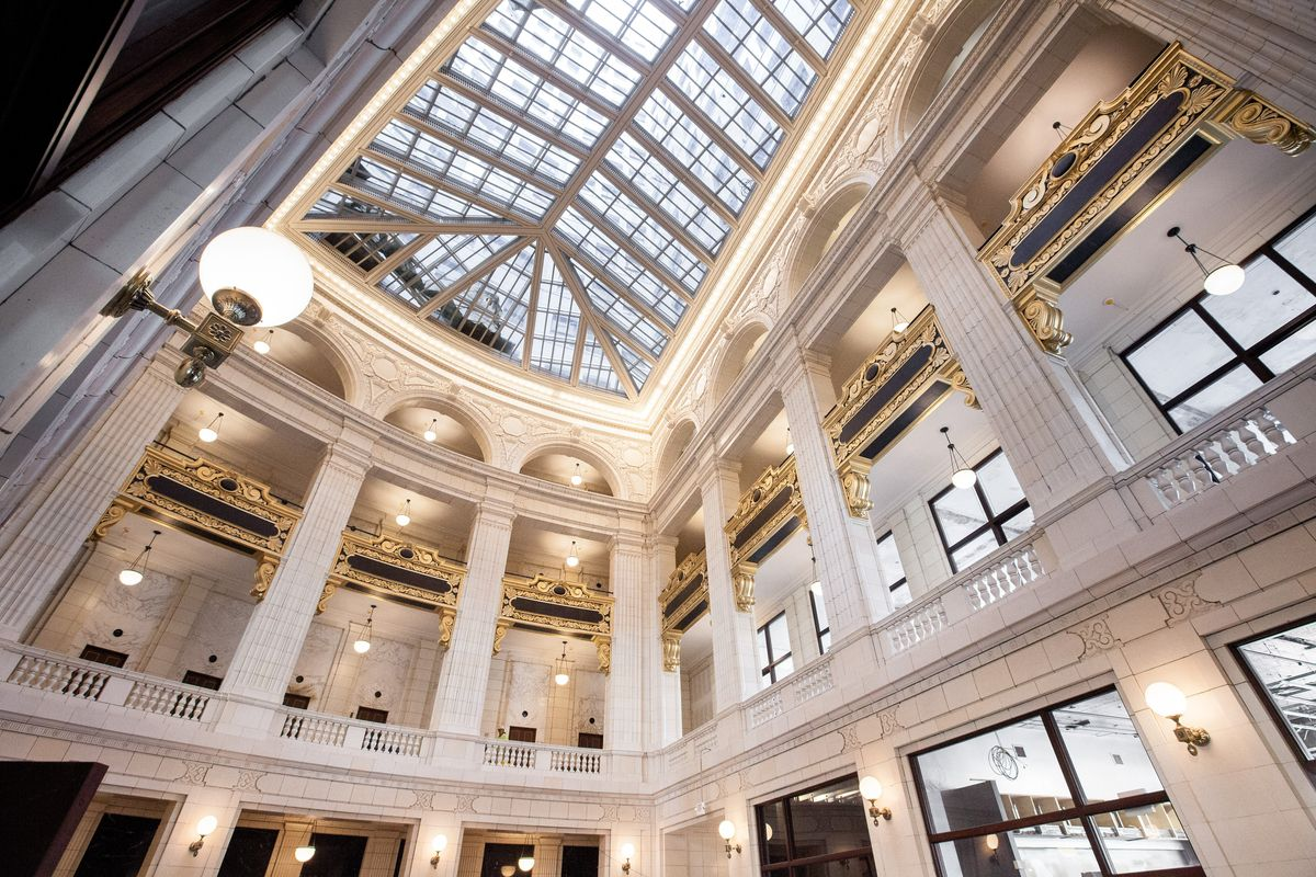 The interior of the David Whitney Building Lobby. There is a glass arched ceiling. The walls are white and there are multiple columns and windows.