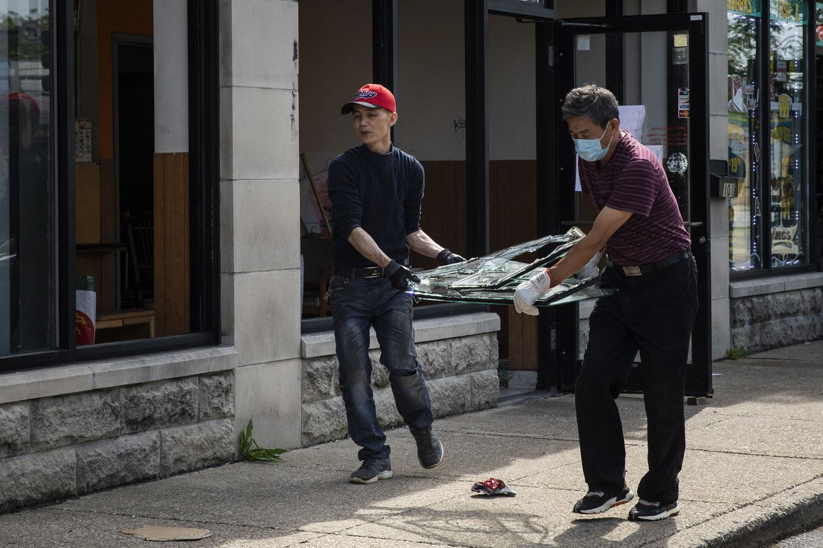The owners of Little Wok at 103 E. 51st St. in Washington Park carry a broken window out of the restaurant Monday after it was looted over the weekend.