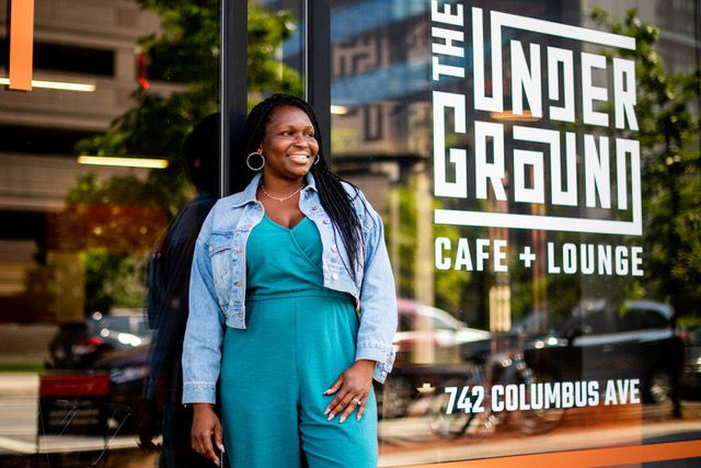 """A woman with long braided hair stands smiling and looking off to the side in front of a glass window. Large white letters on the window say """"The Underground Cafe + Lounge"""" and an address, 742 Columbus Ave. The woman wears a teal romper with a denim jacket over it."""