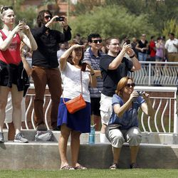 Students, faculty and onlookers watch as the space shuttle Endeavour flies over the University of Arizona campus in honor of former Congresswoman Gabrielle Giffords and her astronaut husband Mark Kelly, both of whom watched the event from a private viewing area, before continuing its trek west to retirement in a Los Angeles museum, at the University of Arizona Thursday, Sept. 20, 2012, in Tucson, Ariz.(AP Photo/Ross D. Franklin)