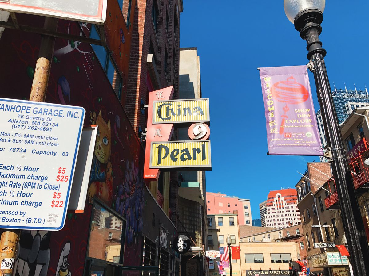 The sign at China Pearl in Boston's Chinatown. It is yellow with red accents and black font.