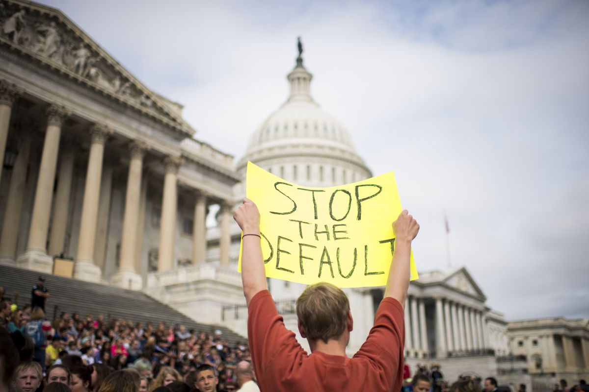 """A protester holds up a sign that reads, """"Stop the default"""" in front of the US Capitol building."""