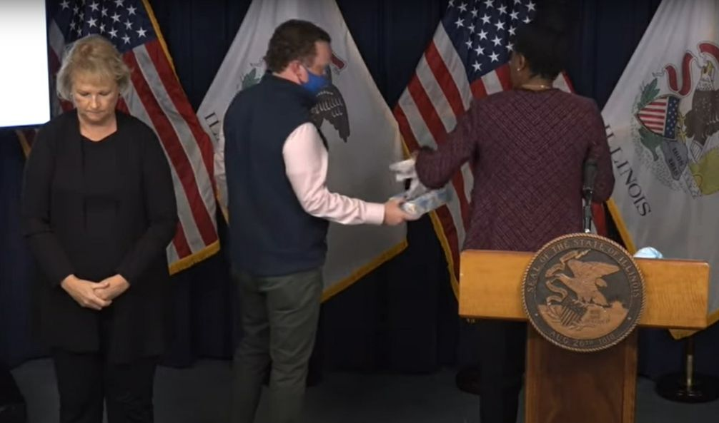 Dr. Ngozi Ezike is offered tissues during Friday's daily coronavirus briefing.