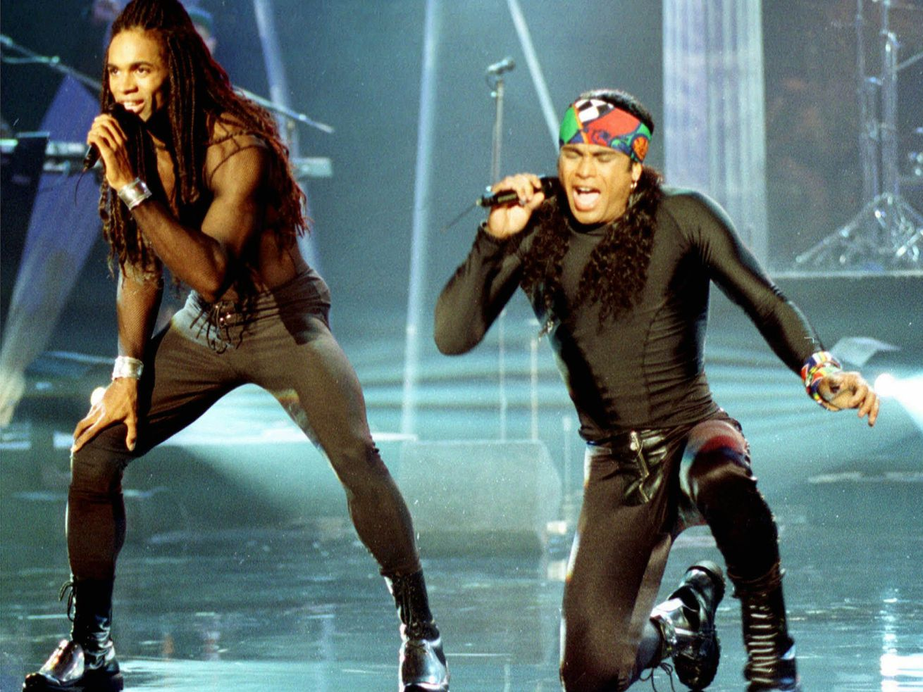 """Fabrice Morvan (left) and Rob Pilatus of Milli Vanilli perform during the taping of """"The Arsenio Hall Show"""" in Los Angeles in 1992. John Davis, one of the real singers behind the lip-synching duo, died of the coronavirus this week."""
