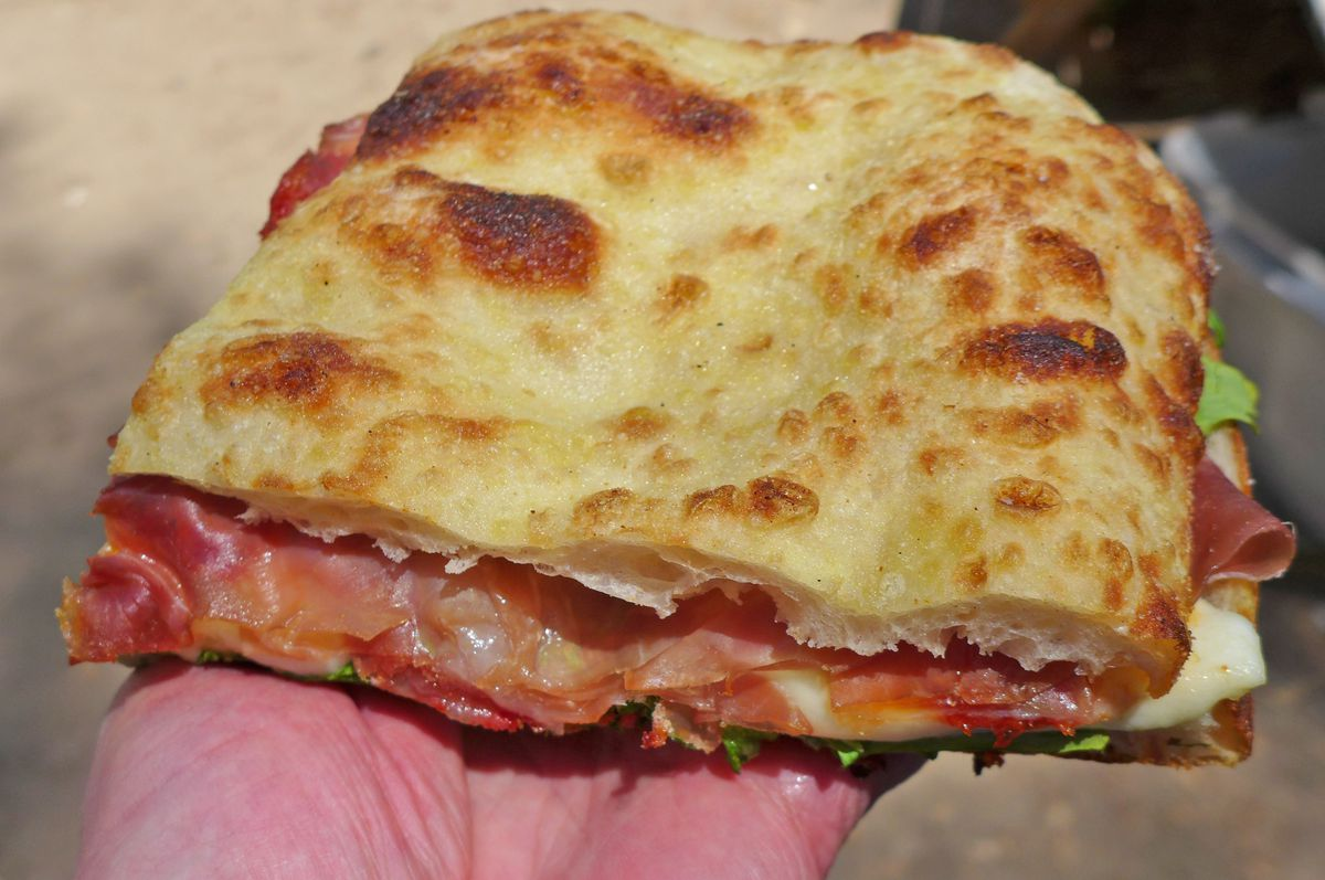 Flatbread held in the palm of a hand made into a prosciutto sandwich.