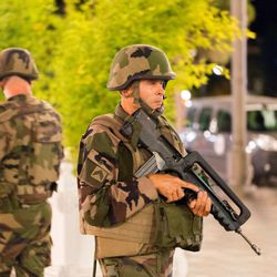 """French soldiers stand guard by the sealed off area of an attack after a truck drove on to the sidewalk and plowed through a crowd of revelers who'd gathered to watch the fireworks in the French resort city of Nice, southern France, Friday, July 15, 2016. A spokesman for France's Interior Ministry says there are likely to be """"several dozen dead"""" after a truck drove into a crowd of revelers celebrating Bastille Day in the French city of Nice. (AP Photo/Ciaran Fahey)"""