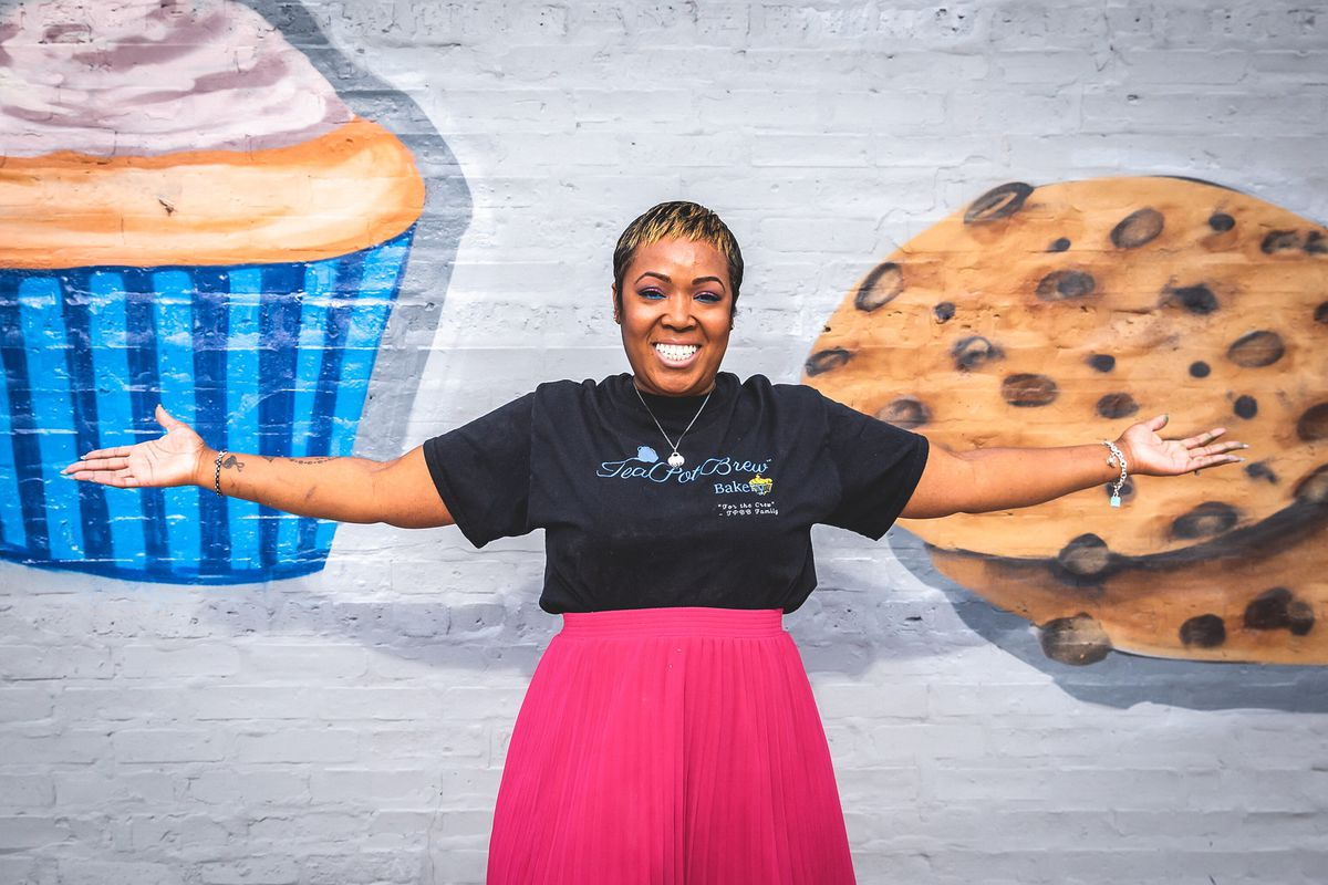 A woman with her hands stretched in front of a mural of cupcake and cookie.