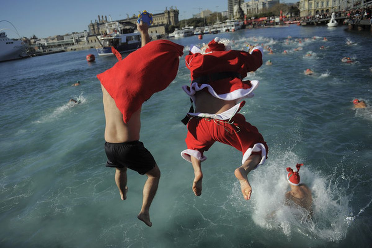 A competitor dressed up as Santa Claus jumps into the sea during the 101st Barcelona's Traditional Christmas Swimming Cup at the Old Harbour of Barcelona on December 25 2010 in Barcelona Spain.
