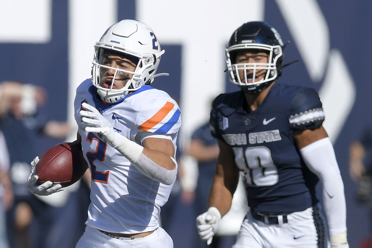 Boise State wide receiver Khalil Shakir runs down the field after catching a pass as Utah State linebacker AJ Vongphachanh defends.