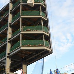 6:45 p.m. The batting practice net being lowered in front of the left field video board -