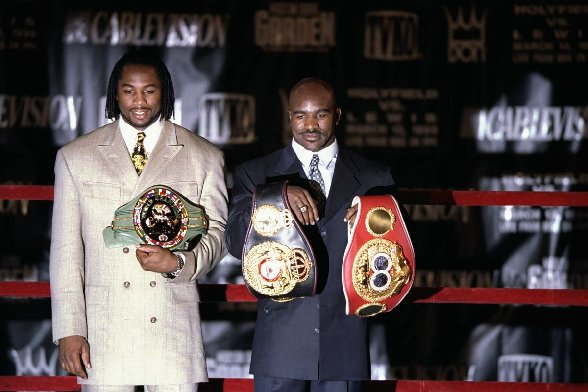 Evander Holyfield and Lennox Lewis hold their title belts before a pre-fight press conference.