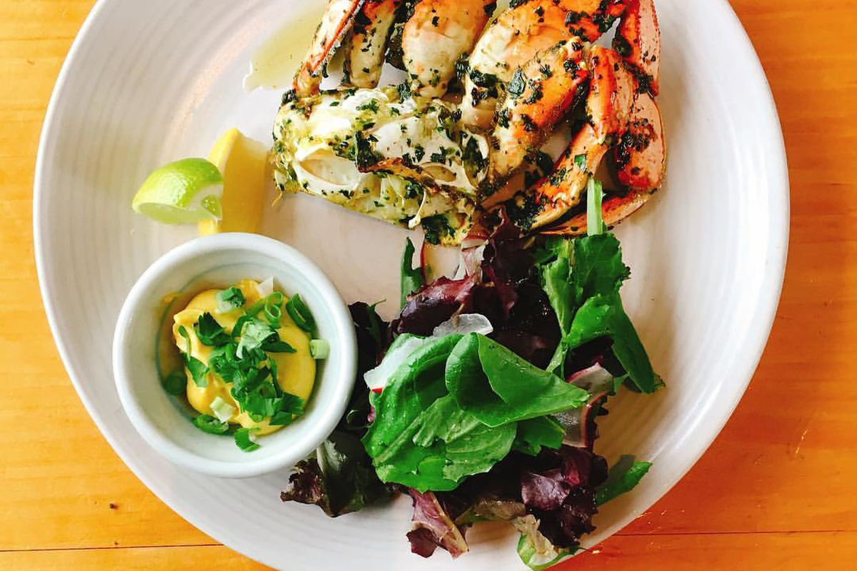 Wood-oven-roasted half Dungeness crab on a white plate