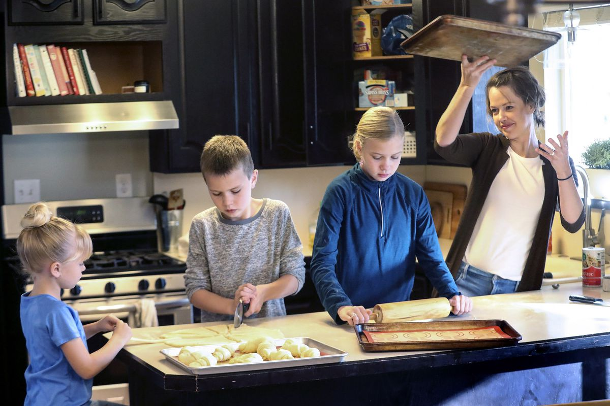 Emily White, right, moves a tray of rolls to the oven as she bakes with her children Penny, left, Henry and Ellie in the kitchen of their home in Holladay on Wednesday, Nov. 25, 2020. The family started a bakery two years ago and has been baking loaves of bread every week, fulfilling neighbors' orders. This year, the family is donating proceeds from Thanksgiving roll sales to foster care agency Brighter Futures to help pay for kids' Christmas presents after Utah and Salt Lake counties notified the agency they can't give it funding for gifts this year.