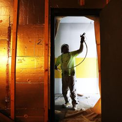 Eloy Guerrero paints a door frame in Salt Lake City on Thursday, Feb. 2, 2017, during construction of the 9th East Lofts at Bennion Plaza. The building will provide 68 affordable apartments.