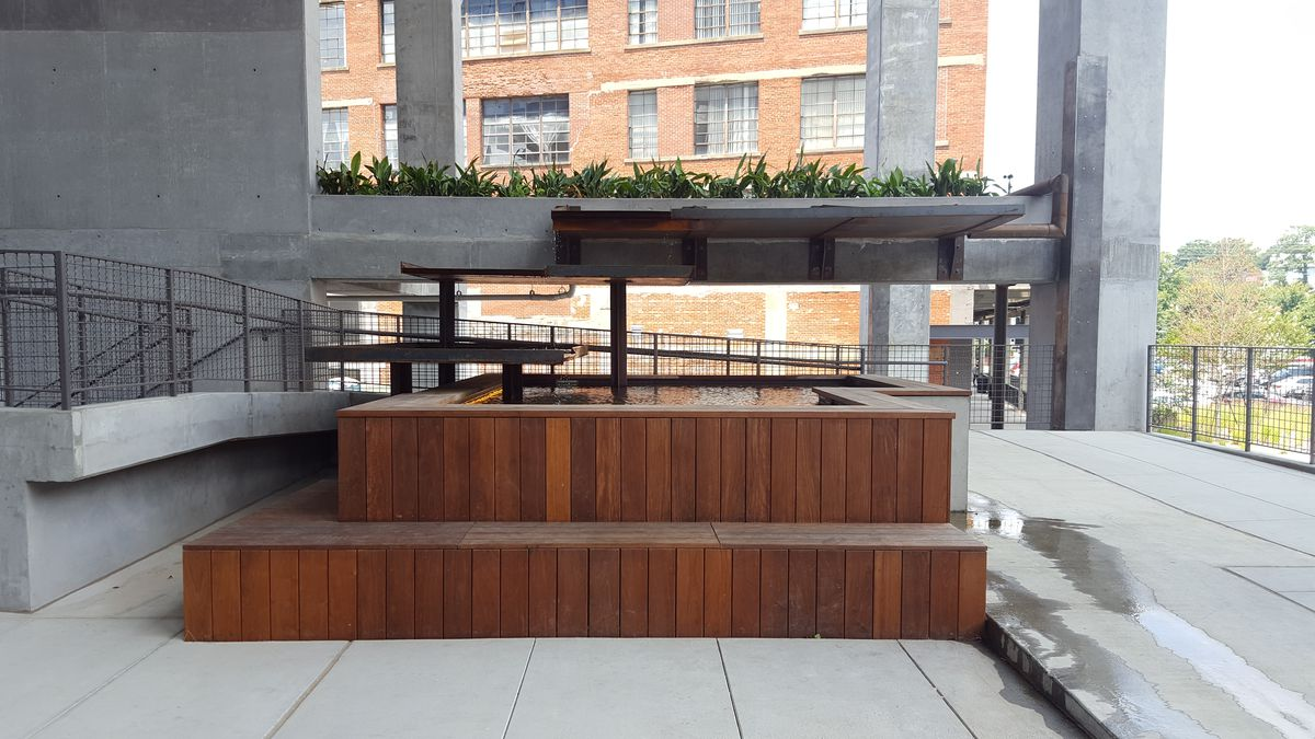 A wooden bench is part of a metal water fountain.