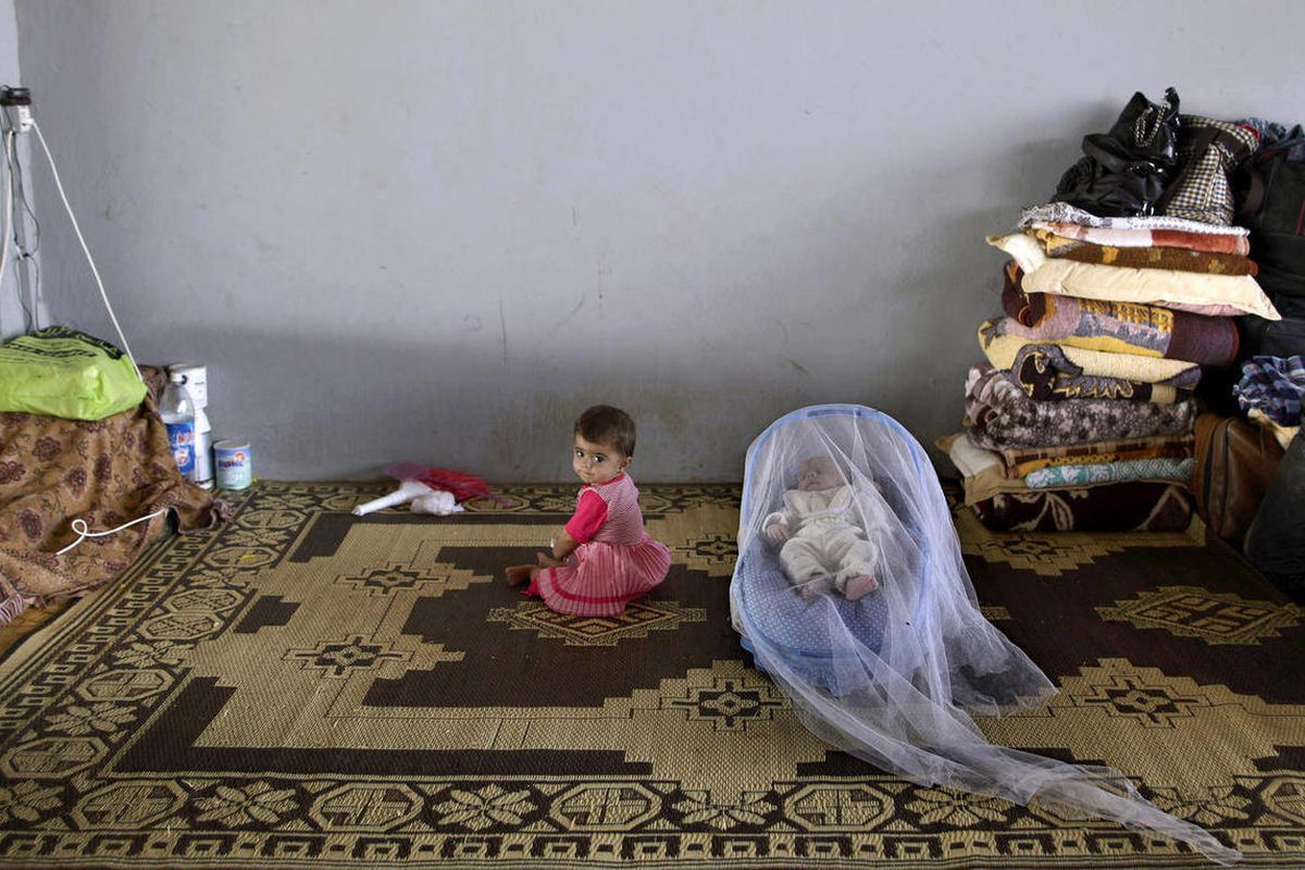 Syrian child, Taybah Al-Hajji, 1, whose family fled their home in Aleppo 15 days ago due to Syrian government shelling, sits next to her one month old brother Abdulghani, sleeping in a child safety seat covered with a mosquito net, as they take refuge wit