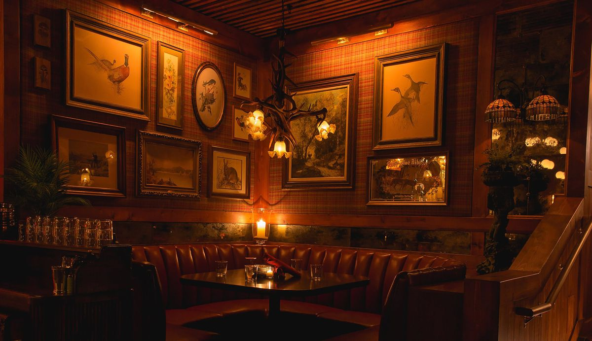 A leather-upholstered corner banquette in a low-lit restaurant with a light fixture made of antlers