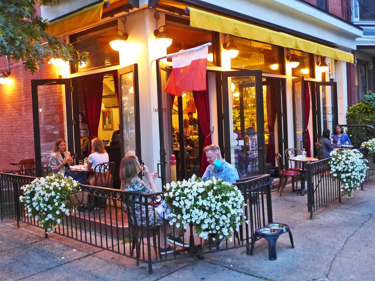 A restaurant open at the sides with flower bedecked tables outside.
