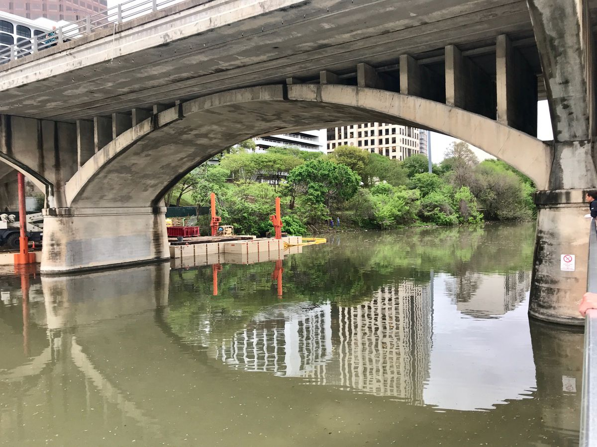 Large concrete bridge over a river with construction equipment underneath on one side