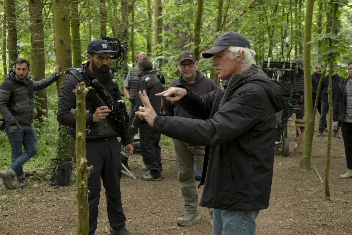 roger deakins uses his fingers to explain a shot in a forest to his onlooking crew