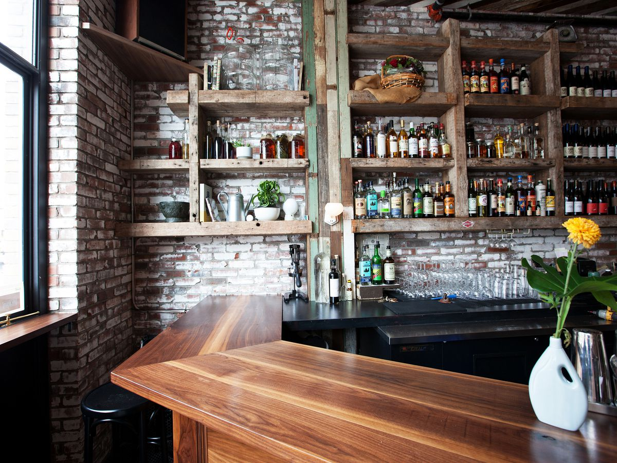 A curved wooden bar with dozens of wine bottles arranged on floating shelves.