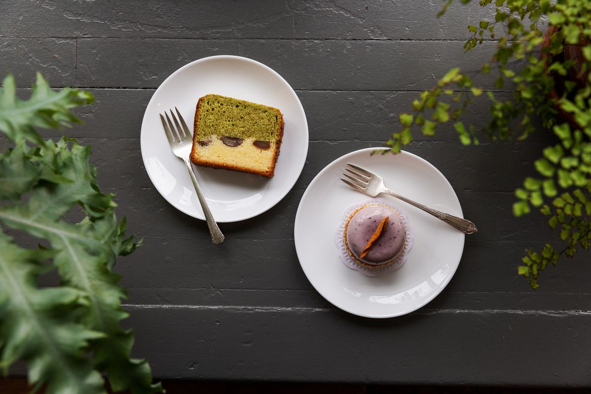 Chestnut cake with white and matcha green marbling and a purple ube pastry surrounded by green plants and delicate forks.