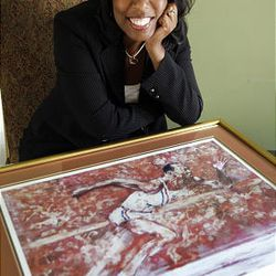 Marlene Dortch, granddaughter of Jesse Owens, poses for a photograph with a Leroy Neiman print of her grandfather, in her home in Fort Washington, Md., Tuesday.