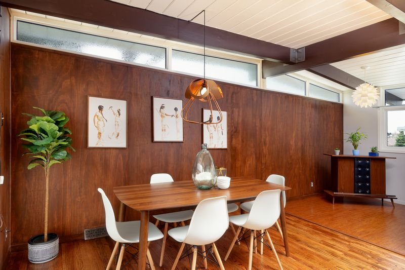 A dining room has a wooden table with six white midcentury inspired dining room chairs.