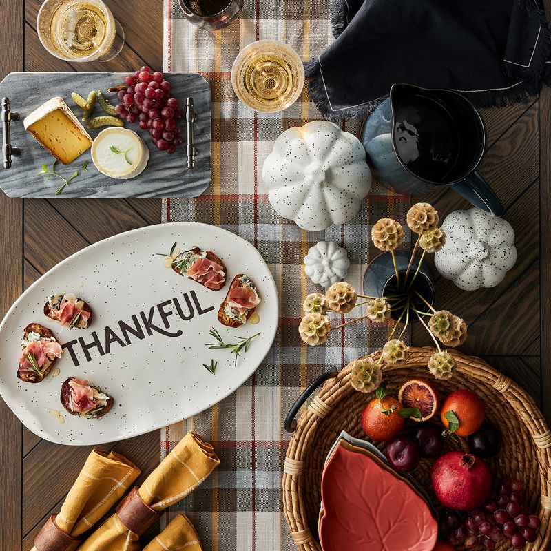 Thanksgiving dinner spread with a plate that says the word thankful on it.