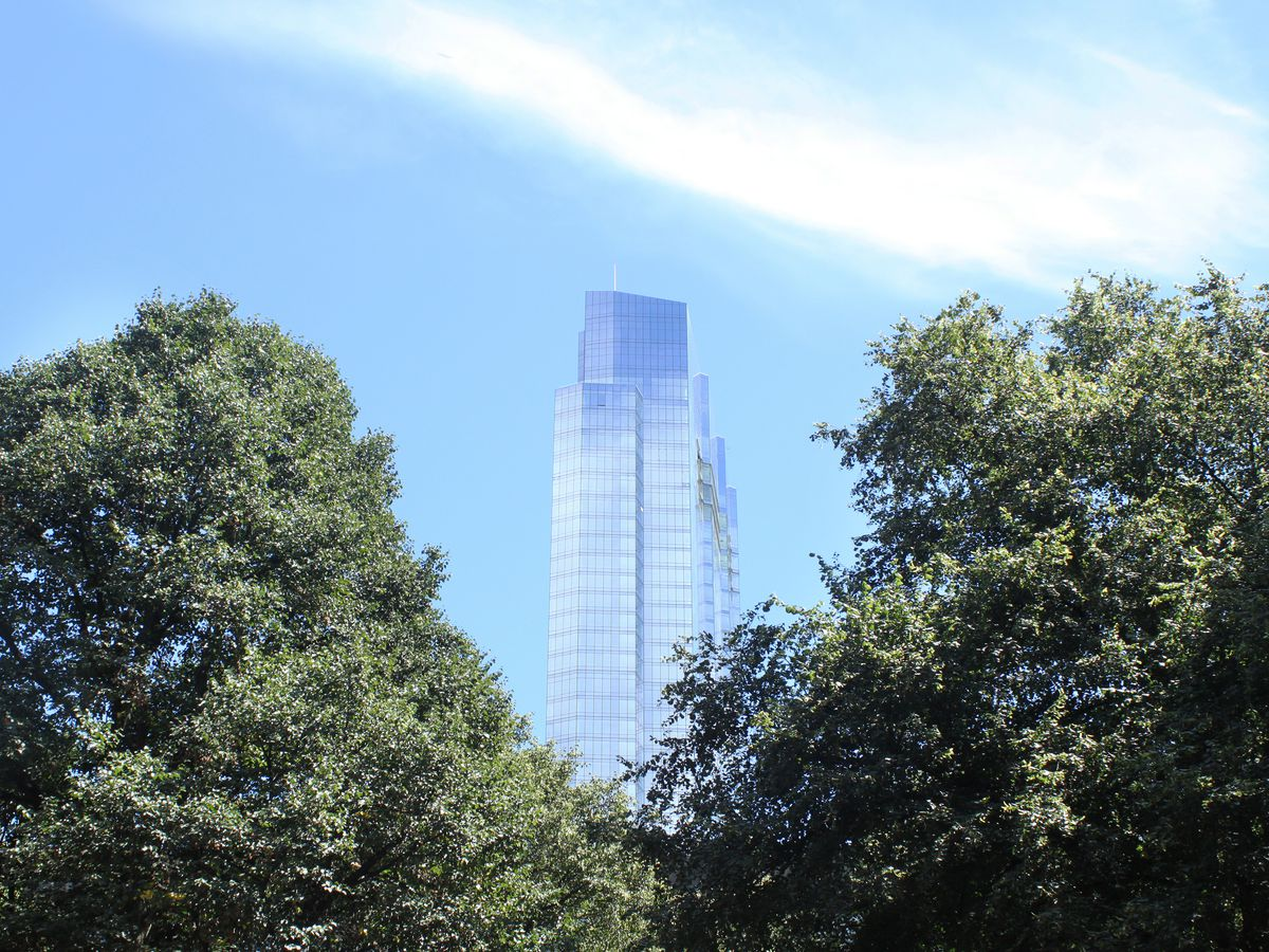 In the foreground are trees. In the distance is a tall glass skyscraper.