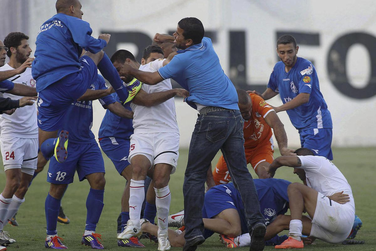 In this photograph made on Friday, May 20, 2012, players of Hapoel Ramat Gan and Bnei Lod fight during a second-division game In Ramat Gan, Israel. A wave of violence has jolted football in Israel, resulting in police investigations, stiff punishments and