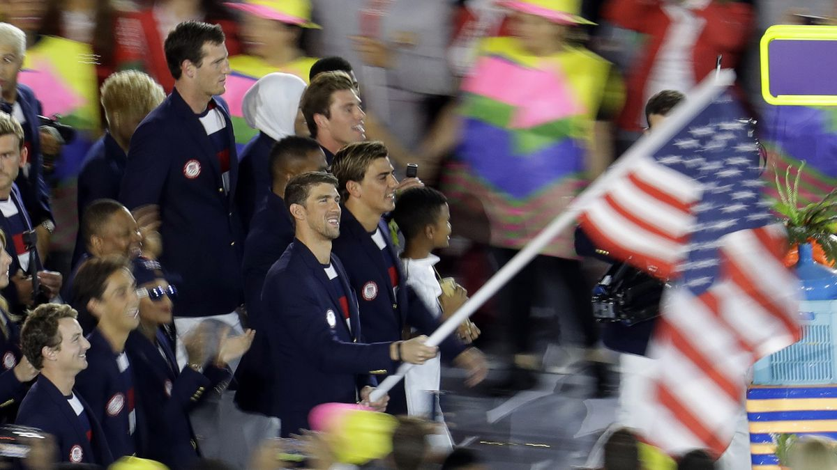 Michael Phelps carries the flag of the United States during the opening ceremony for the 2016 Summer Olympics.