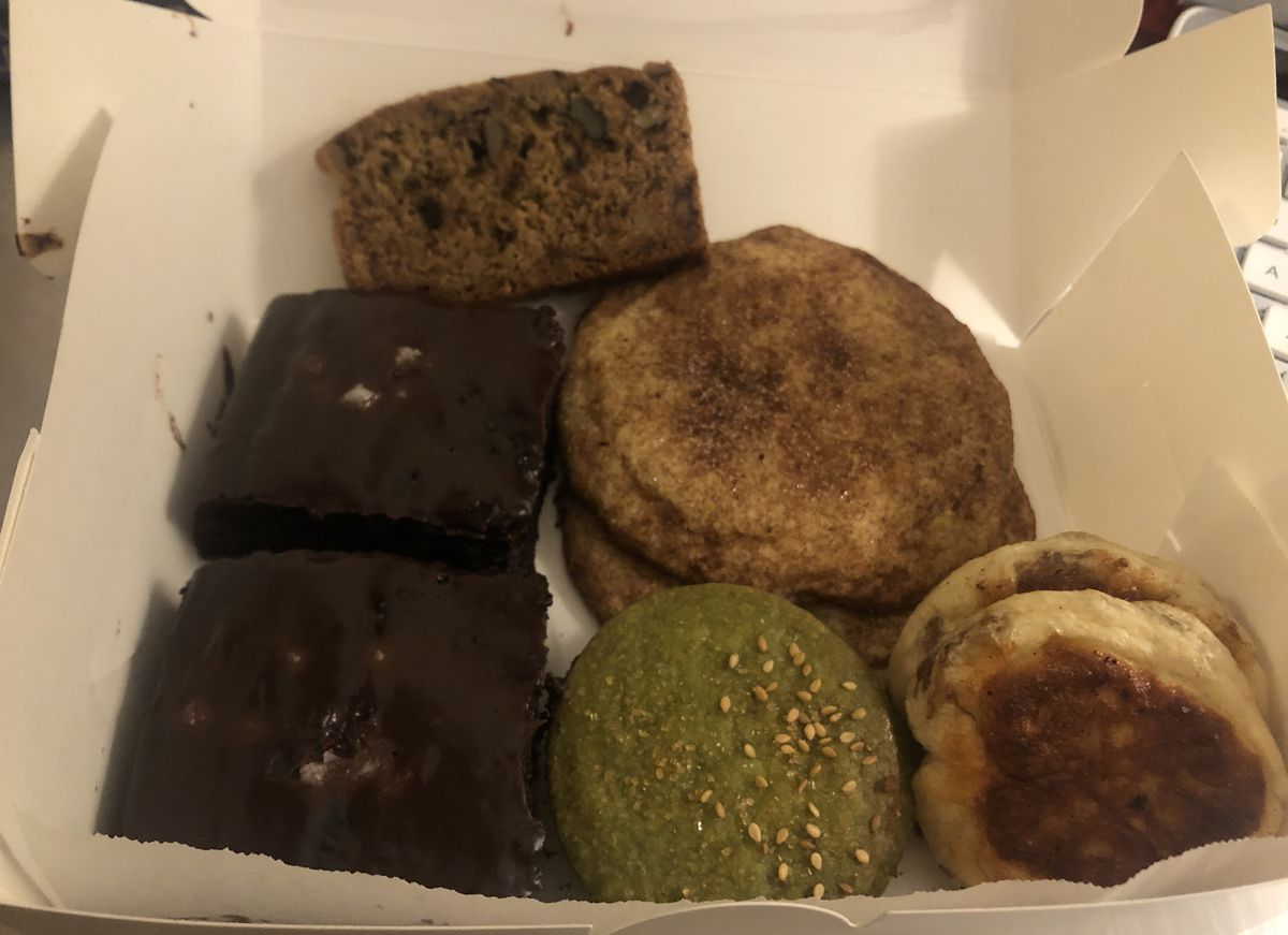 A white cardboard box filled with chocolate cake, snickerdoodle cookies, green matcha shortbread cookies, and more