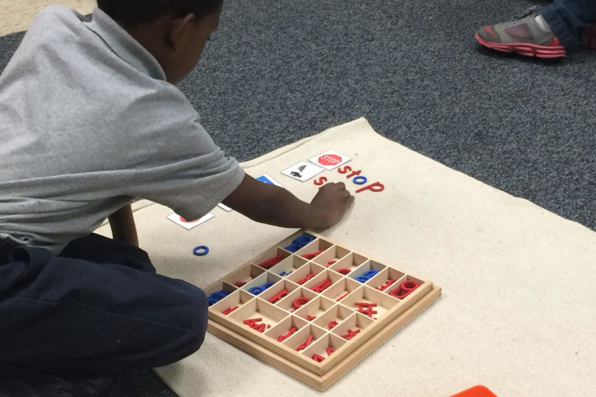 A student at Libertas School of Memphis spells out words next to pictures as part of his independent learning time at the Montessori school in the Frayser community.
