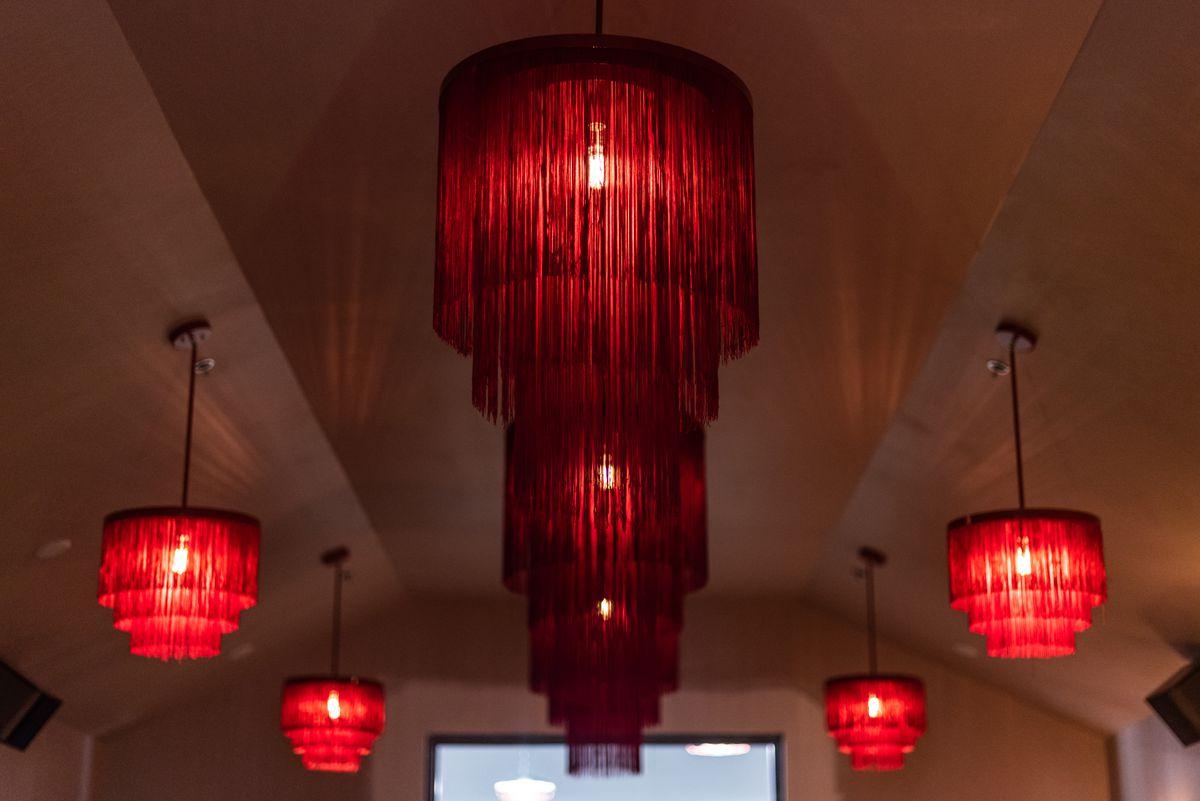 five red fringe vintage chandeliers on the ceiling at Wonderkid